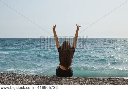 Young Happy Girl Is Warming Up And Relaxing On A Stone Beach, Lying And Sitting On The Rocks, The Se