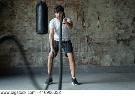 Powerful Man Training With Rope In Functional Training Fitness Gym. Crossfit Ropes Exercise During A