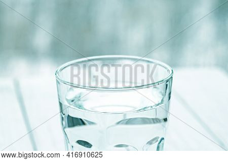 A Glass With Pure Clear Melt Water Stands On A White Table