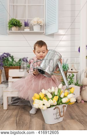 Little Girl One Year Old Plays In Backyard With Metal Watering Can Watering Tulips Flowers. Free Tim