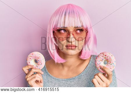Young caucasian woman wearing pink wig holding donuts smiling looking to the side and staring away thinking.