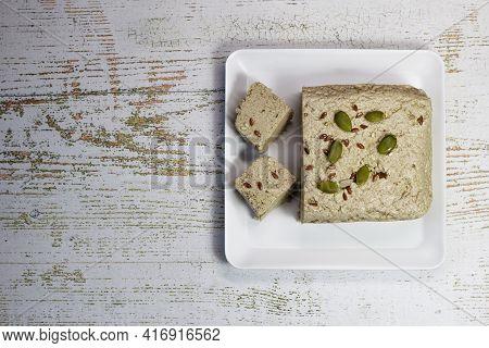 Halva On A White Plate On A White Wooden Background. Traditional Oriental Dessert Sweet Halva. Halva