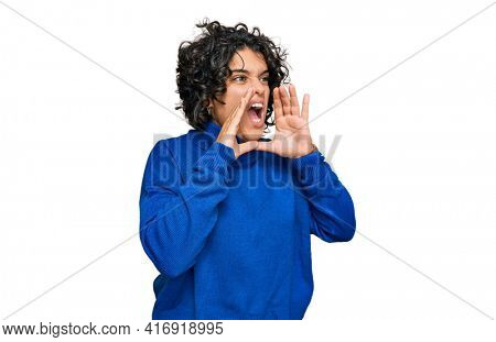 Young hispanic woman with curly hair wearing turtleneck sweater shouting angry out loud with hands over mouth