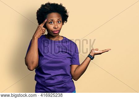 African american woman with afro hair wearing casual purple t shirt confused and annoyed with open palm showing copy space and pointing finger to forehead. think about it.
