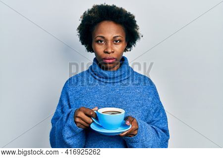 Young african american woman drinking a cup of coffee skeptic and nervous, frowning upset because of problem. negative person.