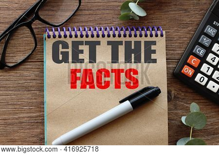 Get The Facts, .text On Craft Paper On Wood Background Near Calculator.