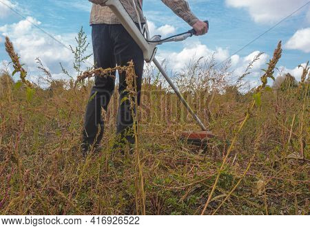 A Worker Cuts Huge Weeds With A Brush Cutter. The Figure Of A Farmer Holding A Trimer. Back View. Cl