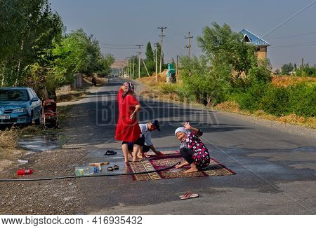 Kazarman. Kyrgyzstan. August 12, 2019. The Family Of A Suburban Village Wash Carpets In The Middle O