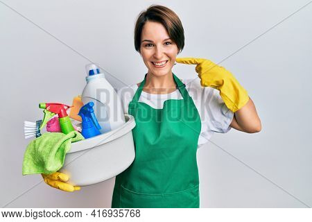 Young brunette woman with short hair wearing apron holding cleaning products smiling cheerful showing and pointing with fingers teeth and mouth. dental health concept.
