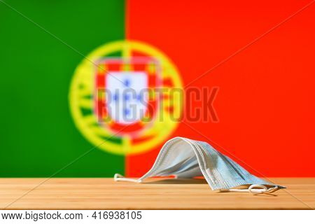 The Medical Mask Lies On The Table Against The Background Of The Flag Of Portugal. The Concept Of A