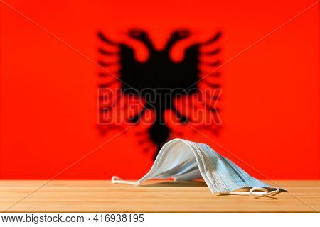 A Medical Mask Lies On The Table Against The Background Of The Flag Of Albania. The Concept Of A Man