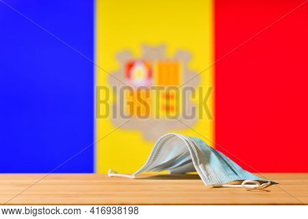 A Medical Mask Lies On The Table With The Andorran Flag In The Background. The Concept Of A Mandator
