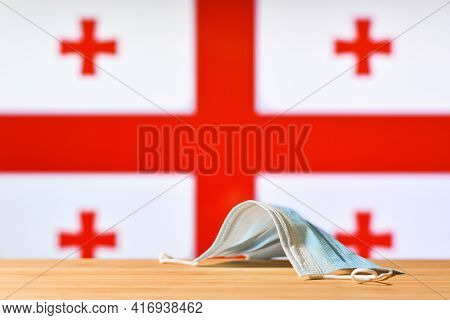 A Medical Mask Lies On The Table Against The Background Of The Flag Of Georgia. The Concept Of A Man