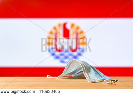 A Medical Mask Lies On The Table Against The Background Of The Flag Of French Polynesia. The Concept