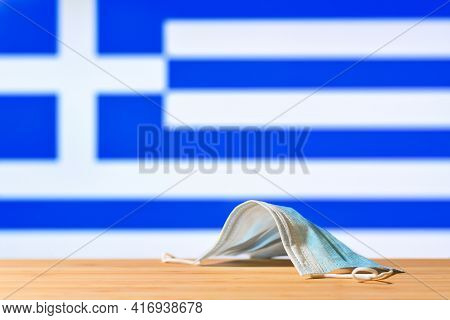 A Medical Mask Lies On The Table Against The Background Of The Flag Of Greece. The Concept Of A Mand