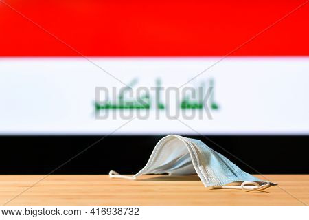 A Medical Mask Lies On The Table Against The Background Of The Flag Of Iraq. The Concept Of A Mandat