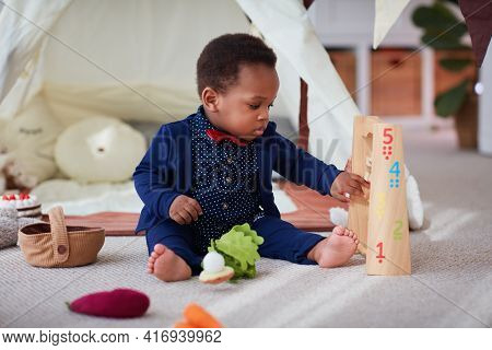 Cute Little Baby Boy Playing With Wooden Developing Toy On The Carpet At Home