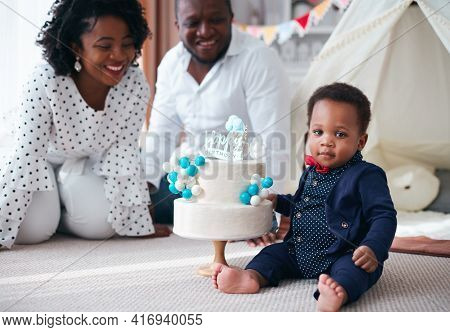 Happy One Year Old Baby Boy With Birthday Cake And Happy Parent On The Background