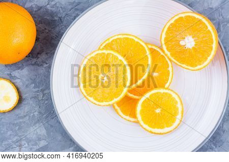 Pieces Of Fresh Orange On A Plate On The Table. Vitamins, Diet And Vigor. Close-up