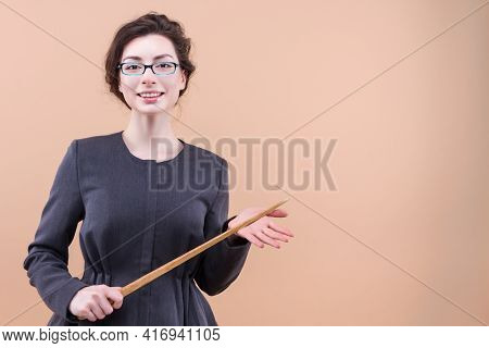 Portrait Of Teacher Keeping Wooden Pointer Showing Blank Space, Smiling Isolated On Pastel Beige Col