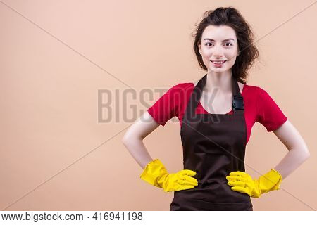 Young Smiling Brunette Woman With Curly Hair Wearing Cleaner Apron And Rubber Yellow Gloves Isolated