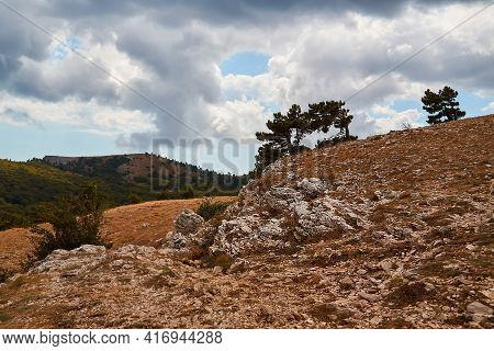 Rocky And Hilly Terrain. Grey Cloudy Sky. Mountain On Background. Summer, Autumn Season. Wild Nature