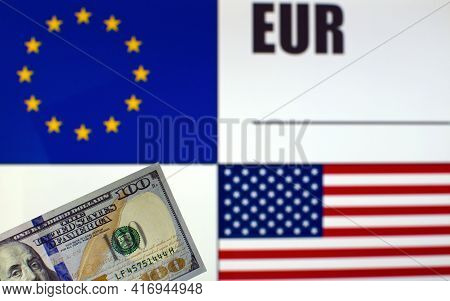 100 Us Dollars Banknote On Blurred Background Of Eu And Us Flags And Eu Currency Code. Exchange Rate