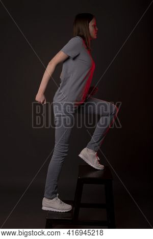Young Woman Walking Up Stairs, Upstairs On Black Background. Concept Of Aspirations, Self Growing, P