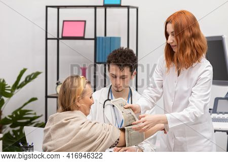 A Nurse Places A Blood Pressure Monitor On A Patients Arm To Check Blood Pressure. The Primary Care