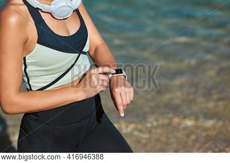 Training Out On Fresh Air. Sport Time And Fitness Idea. Female Sets Timer For Workout. Lady In Sport
