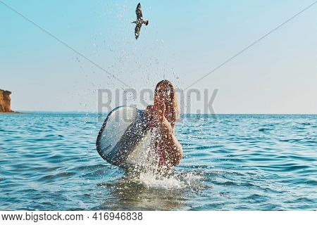 Woman Having Fun In Ocean, Spray With Water. Bird Flying In Blue Sky. Holiday Trip, Surfing Sport An