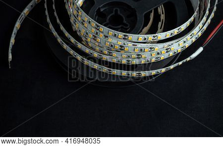 Reel With Led Strip For Voltage Of 12 Volts On A Black Background.