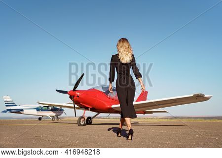 Back View Fashionable Women In Beautiful Classy Black Dress Walking To A Red Private Plane And Blue