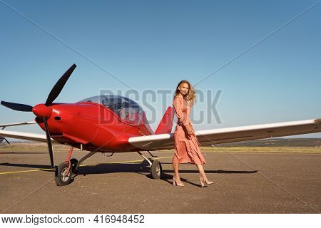 Pretty Blond Woman With Wavy Hair Wearing Pink Silk Classy Dress Posing Near A Private Plane