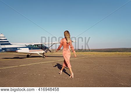 Back View Fashionable Women In Beautiful Classy Pink Dress Walking To A Private Plane And Blue Sky I