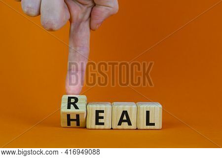 Real Heal Symbol. Doctor Turns A Wooden Cube With Words 'real Heal'. Beautiful Orange Background, Co