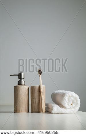 Bamboo Toothbrushes, Toothpaste, White Towel On The Gray Table. Bathroom, Ecological Dental Care Pro