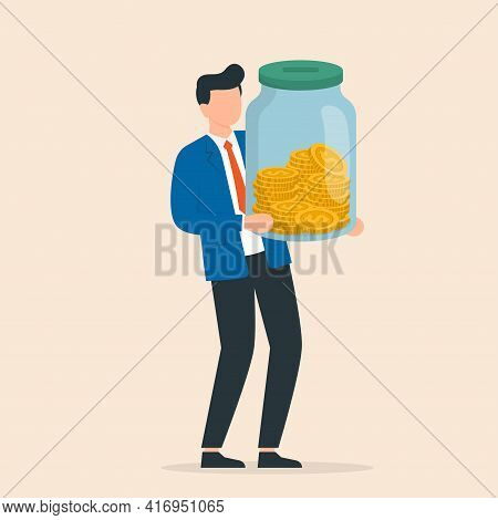 Businessman Holding Glass Jar With Full Of Coins. Saving Income In Glass Bottle For Retirement Or De