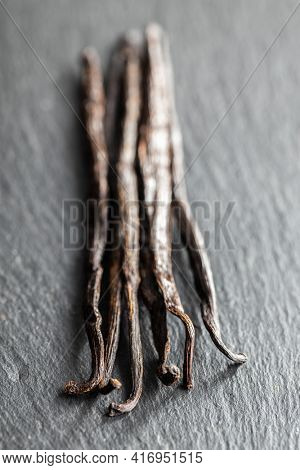 Vanilla pods. Sticks of vanilla on black table.
