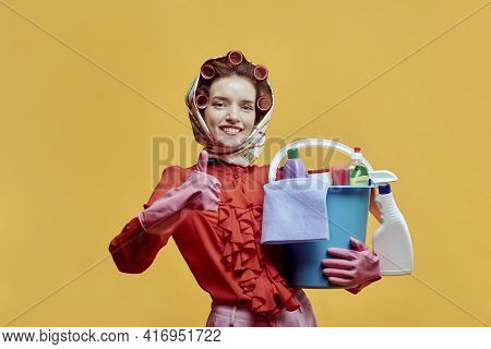 A Female Cleaner Holds A Bucket Of Cleaning Tools And Shows A Thumbs-up Gesture.