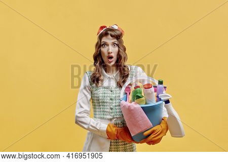 A Surprised Woman Cleaner Holds A Bucket With Tools For Cleaning The House.