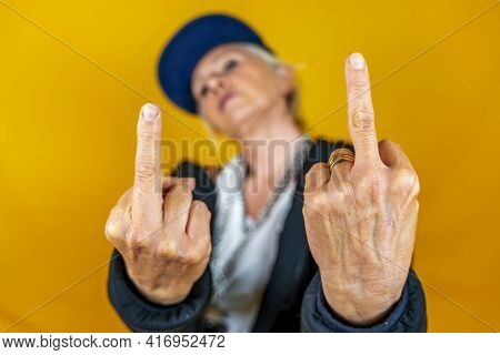 Funny Portrait Of Mature Woman. Lady Shows The Middle Finger  Dressed As An Angry Rapper