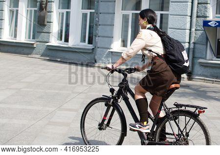 Pretty Girl Rides A Bicycle Along The City Street. Ukraine Zhytomyr 12 April 2021