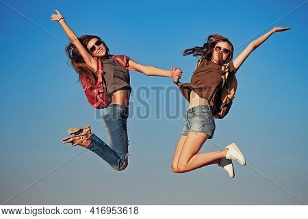 Happy Girls Jumping On Sky. Two Pretty Women In Jeans And Shorts With Backpacks Outdoor On Sunny Day
