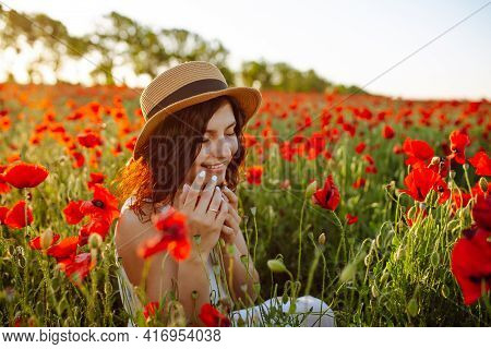 Young Woman Sits In The Middle Of The Red Poppy Field And Smells The Flowers. Girl Enjoys A Good Sun