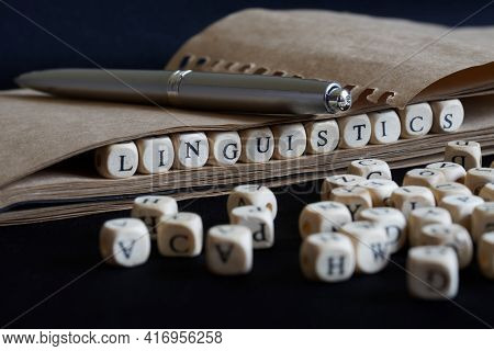 Notepad, Fountain Pen And The Word Linguistics Made Up Of Wooden Cubes On A Dark Background. A Conce