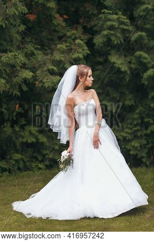 Beautiful Bride In A Magnificent Wedding Dress Posing Among Greenery On The Street. Bride Concept Fo