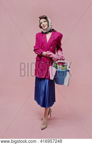 A Woman In A Jacket And Skirt Holds A Bucket Of Cleaning Tools, At Full Height.