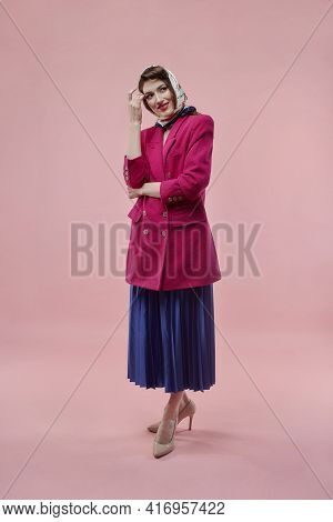 A Beautiful Brunette Woman In A Pink Jacket And A Long Blue Full-length Skirt.