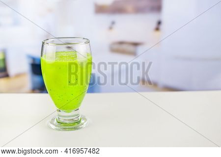 Glass Of Juice With Cucumber And Parsley On White Table, Detox Cocktail Of Raw Fruits And Vegetables